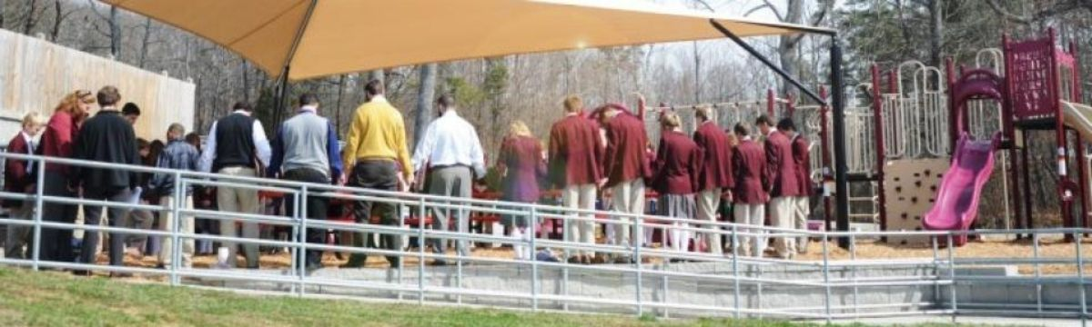 Teachers and students praying to dedicate new school playground